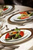 Wedding tables with green salad. Tables set for fine dining during a wedding event. Plates of salad as an appetizer Stock Images