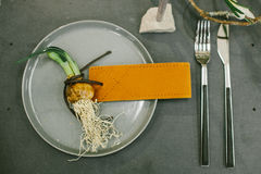 Wedding tableware, onion of narcissus with leather name card, silver fork and silver knife. Stock Photos