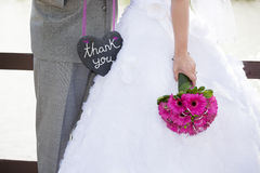 Wedding Thank-You. A bride and groom holding a heart shaped thank-you sign Royalty Free Stock Photography