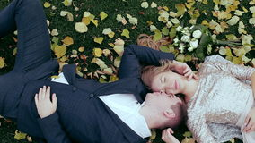 Wedding theme, the bride and groom are in the maple leaves on grass. Elegant couple lies on the grass leaves stock footage