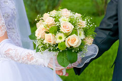 Wedding theme, hands and rings on wedding bouquet Royalty Free Stock Image