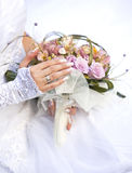 Wedding time. Hands and rings on wedding bouquet Stock Photo