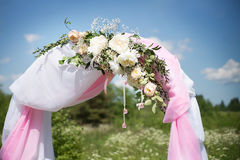 Wedding traditional arch with flower decor on blue sky background Stock Photo
