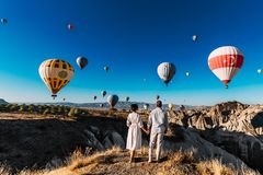 Wedding travel. Honeymoon trip. Couple in love among balloons. A guy proposes to a girl. Couple in love in Cappadocia. Couple in royalty free stock images