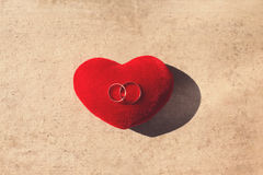 Wedding two gold rings on a red pillow heart shape over craft paper background. Wedding two gold rings on red pillow heart shape over craft paper background stock image