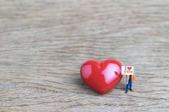 Wedding or valentines card and background, miniature people, man. Holding sign board with text I love you asking for love with red heart shape on wood table Royalty Free Stock Photography