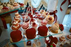 Wedding variety dessert cakes with tasty buffet color decorated with whipped cream, candy bar, buffet, red valentine`s heart.  Royalty Free Stock Photography