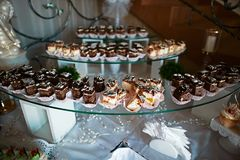 Wedding variety dessert cakes with tasty buffet color decorated with whipped cream, candy bar, sweet buffet on a glass tray.  Stock Photos