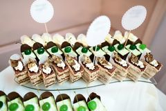 Wedding variety dessert cakes with tasty buffet color decorated with whipped cream and green cherries, candy bar, sweet buffet.  Royalty Free Stock Photo
