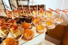 Wedding variety dessert cakes with tasty buffet color decorated with whipped orange cream, candy bar, buffet.  Royalty Free Stock Photos