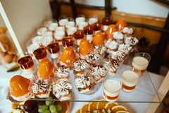 Wedding variety dessert cakes with tasty buffet color decorated with whipped orange cream, candy bar, sweet buffet.  Royalty Free Stock Photos