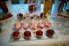 Wedding variety dessert cakes with tasty buffet color decorated with whipped red cream, candy bar, a buffet on a glass tray.  Royalty Free Stock Photos