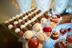Wedding variety dessert cakes with tasty buffet color decorated with whipped red cream, candy bar, buffet.  Royalty Free Stock Photo