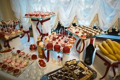 Wedding variety dessert cakes with tasty buffet color decorated with whipped red pearl cream, candy bar, buffet on a glass tray.  Royalty Free Stock Photo