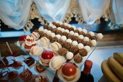 Wedding variety dessert cakes with tasty buffet color decorated with whipped red pearl cream, candy bar, buffet on a glass tray.  Stock Photo