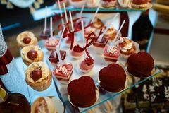 Wedding variety dessert sweet muffins, cakes with tasty buffet color decorated with whipped cream, candy bar, buffet, red valentin. E`s heart Royalty Free Stock Photos