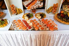 Wedding variety fruits and dessert cakes with tasty buffet color decorated with whipped orange cream, candy bar, buffet on the mir. Ror tray Royalty Free Stock Photo