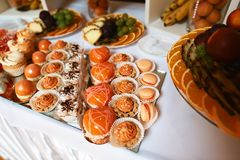 Wedding variety fruits and dessert cakes with tasty buffet color decorated with whipped orange cream, candy bar, buffet on the mir. Ror tray Stock Photo