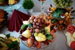 Wedding various fresh fruits and berries with tasty colour on a buffet table, grapes, pears and mint leaves Royalty Free Stock Image