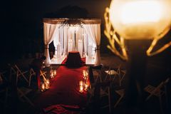 Wedding venue aisle with candles in glass lanterns and arch, sty. Lish wedding decor for evening wedding ceremony in garden, light close up. beautiful romantic royalty free stock image