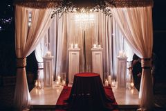 Wedding venue aisle with candles in glass lanterns and arch, sty. Lish wedding decor for evening wedding ceremony in garden, light close up. beautiful romantic royalty free stock photography