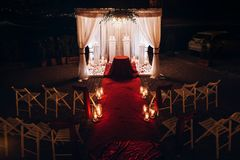 Wedding venue aisle with candles in glass lanterns and arch, sty. Lish wedding decor for evening wedding ceremony in garden, light close up. beautiful romantic stock image