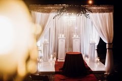Wedding venue aisle with candles in glass lanterns and arch, sty. Lish wedding decor for evening wedding ceremony in garden, light close up. beautiful romantic royalty free stock images