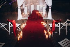 Wedding venue aisle with candles in glass lanterns and arch, sty. Lish wedding decor for evening wedding ceremony in garden, light close up. beautiful romantic stock photography