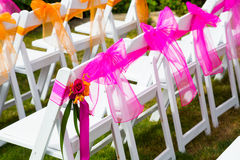 Wedding Venue Chairs. White wedding venue chairs are setup and ready in rows waiting for guests to arrive for the ceremony Royalty Free Stock Images