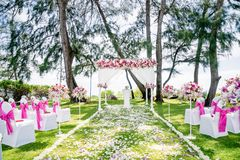 Beach Wedding Venue outdoor with the pine tree and the ocean background, Koh Samui, Thailand. The wedding venue decorated with the banquet chair cover in white Royalty Free Stock Photo