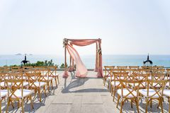 Beach Wedding Venue with the ocean view background, The folding lawn chairs, Koh Samui, Thailand. The wedding venue decorated with the folding lawn chairs with Royalty Free Stock Images