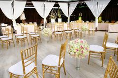 Wedding Venue Decoration, Chairs, Flower. The decoration of wedding venue on the beach, the chairs with white seat, the flower with the glass vast on the floor Royalty Free Stock Images