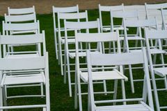 White chairs on wedding venue with green grass on background. Wedding Set Up. Wedding setting. Wedding venue. White chairs on green grass with night lights Royalty Free Stock Photos