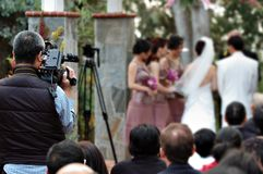 Wedding Videographer. Back of a wedding photographer with bride, groom, and bride maid in the background Royalty Free Stock Image