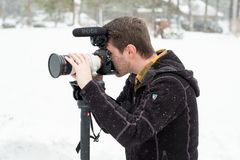 Wedding Videographer at Winter Wedding. SUNRIVER, OR - FEBRUARY 18, 2018: Male wedding videographer at a Winter wedding in Oregon filming in the cold with snow Royalty Free Stock Photos