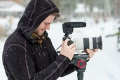 Wedding Videographer at Winter Wedding. SUNRIVER, OR - FEBRUARY 18, 2018: Male wedding videographer at a Winter wedding in Oregon filming in the cold with snow Stock Photography