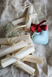 Wedding vintage paper invitation scrolls and blue ceramic heart with red bow on a sackcloth. Stock Photography