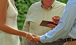Wedding Vows. Groom holding ring and bride's hand during outdoor wedding Royalty Free Stock Photography