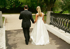 Wedding walk. Newly-married couple go on the bridge to a distance Royalty Free Stock Image