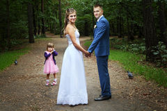 Wedding walk, newlyweds with child walking in forest. Stock Photo