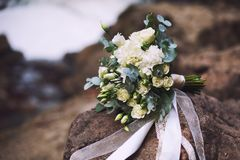 A wedding bouquet of flowers lies on the stones. Wedding white bouquet of flowers with eucalyptus and eutoma on stones Stock Photo