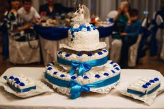 Wedding white cake decorated with blue roses with tiers and cakes and a figure of bride and groom. Wedding white cake decorated with blue roses with three tiers Stock Images