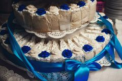 Wedding cake decorated with blue roses with tiers and cakes. Wedding white cake decorated with blue roses with tiers and cakes close up Royalty Free Stock Photography