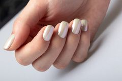 Wedding white pearl manicure on short square nails on a white background close-up stock photo