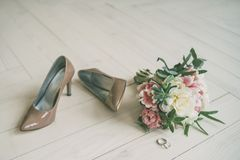 Wedding bouquet and bride`s shoes on the wooden floor. Wedding white pink bouquet and bride`s beige shoes on the wooden floor with rings Stock Photo