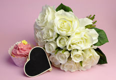 Wedding white roses bouquet with pink cupcake and blank heart sign. Wedding white roses bouquet with pink cupcake with heart shape blackboard with copy space Royalty Free Stock Images