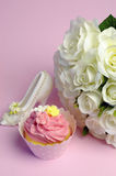 Wedding white roses bouquet with pink cupcake - vertical. Stock Photo
