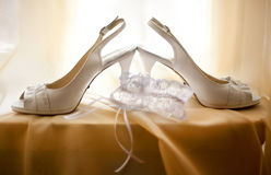 Wedding white shoes and bride`s lace garter Royalty Free Stock Photos