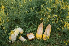 Wedding bouquet, shoes and rings in the grass Stock Photo