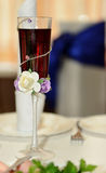 Wedding wine glass. Closeup wuth red drink and roses stock photography